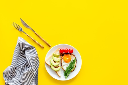 Healthy hearty breakfast. Fried eggs with vegetables near toast with avocado on yellow background top view space for text