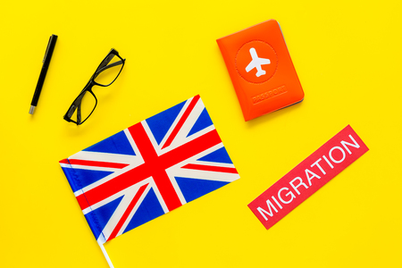 Immigration to Britain concept. Text immigration near passport cover and british flag on yellow background top view