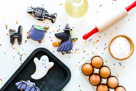 Make halloween gingerbread concept. Icing cookies near rolling pin, baking sheet, eggs, flour on white background top view