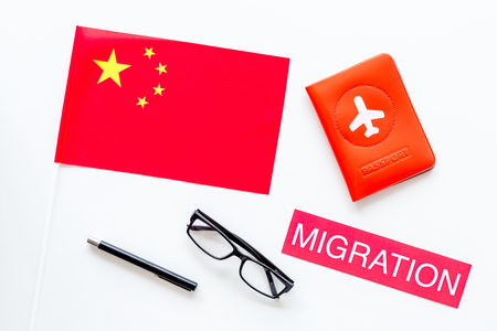 Immigration to China concept. Text innigration near passport cover and chinese flag on white background top view