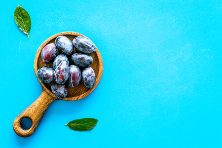 Plums on dinning table. Fresh raw purple plum in wooden bowl on blue background top view copy space