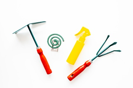 Mosquito protection for garden. Mosquito coil and spray near garden tools on white background top view Banque d'images - 108641828