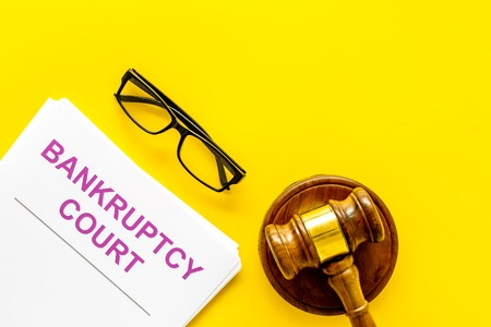 Title of documents the bankruptcy court near judge gavel on yellow background top view copy space
