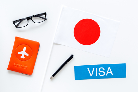Visa to Japan concept. Text visa near passport cover and japanese flag on white background top view Banco de Imagens