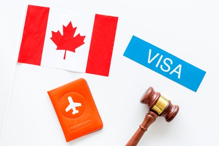 Visa to Canada concept. Text visa near passport cover and canadian flag, hammer on white background top view