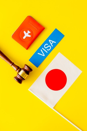 Visa to Japan concept. Text visa near passport cover and japanese flag, hammer on yellow background top view