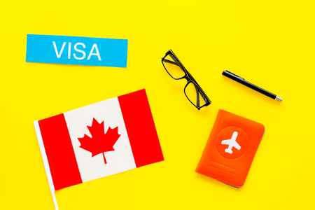 Visa to Canada concept. Text visa near passport cover and canadian flag on yellow background top view