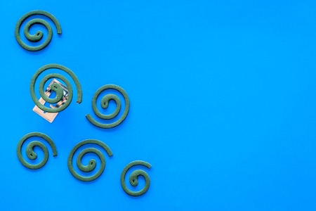 Mosquito repellent for outdoor: garden, summer house, picnic. Green spiral on blue background top view space for text pattern
