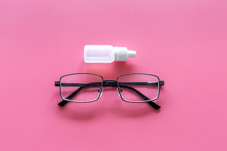 Eye health. Glasses with transparent optical lenses and eye drops on pink background top view copy space closeup