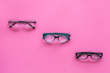 Glasses with transparent optical lenses on pink background top view space for text