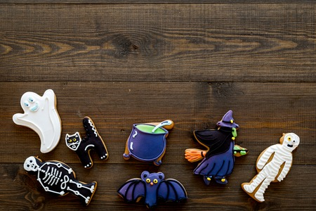 Fresh halloween gingerbread. Icing cookies in shape of halloween evils like black cat, skeleton, bat, ghost, witch on dark wooden background top view copy space Stock Photo