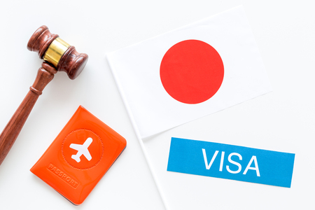 Immigration to Japan concept. Text immigration near passport cover and japanese flag, hammer on white background top view