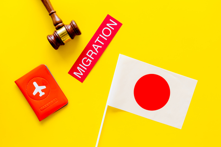 Immigration to Japan concept. Text immigration near passport cover and japanese flag, hammer on yellow background top view