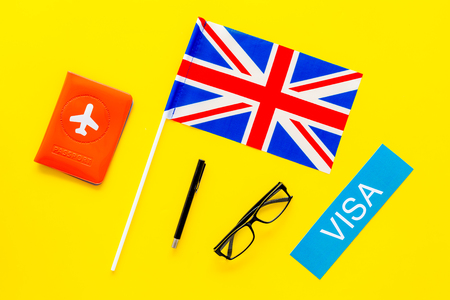Visa to Britain concept. Text visa near passport cover and british flag on yellow background top view