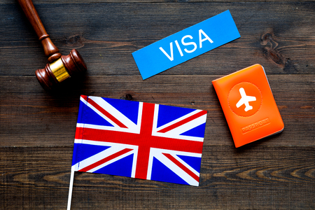 Visa to Britain concept. Text visa near passport cover and british flag, hammer on dark wooden background top view