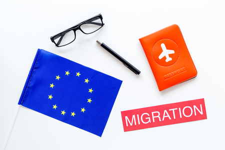 Schengen visa. Immigration to Europe concept. Text immigration near passport cover and european flag on white background top view Banco de Imagens