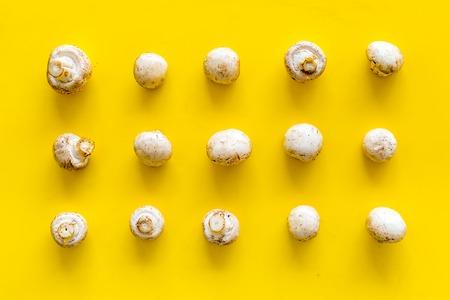 Mushroom champignons pattern. Fresh raw whole champignons on yellow background top view