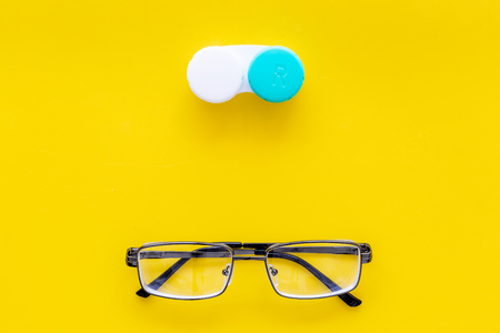 Products help see better. Glasses with transparent optical lenses and eye lenses on yellow background top view space for text closeup Stock Photo