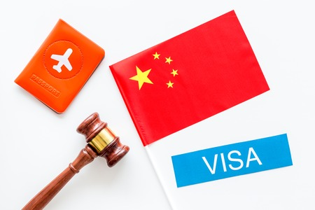 Visa to China concept. Text visa near passport cover and chinese flag, judge hammer on white background top view