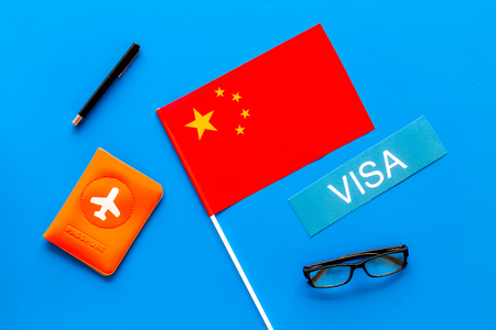 Visa to China concept. Text visa near passport cover and chinese flag on blue background top view