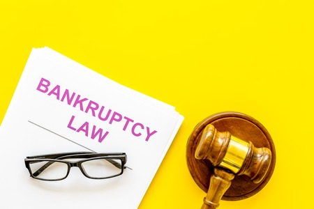 Words bankruptcy law written on the documents near judge gavel on yellow background top view copy space Stock Photo