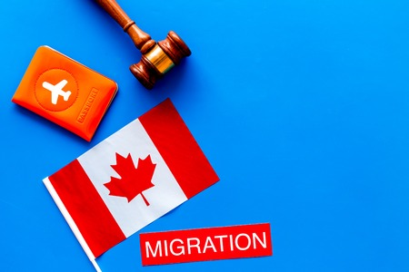 Immigration to Canada concept. Text immigration near passport cover and canadian flag, hammer on blue background top view space for text