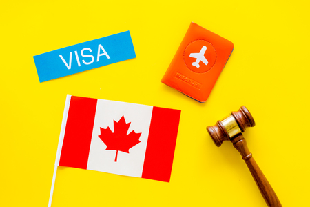 Canada concept. Text  near passport cover and canadian flag, hammer on yellow background top view