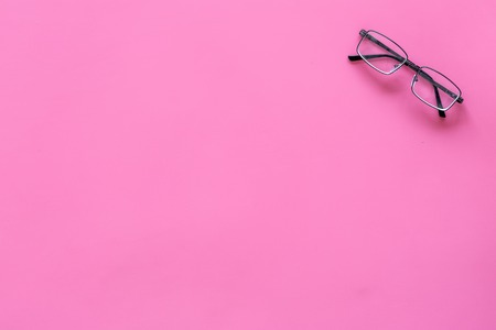 Glasses with transparent optical lenses on pink background top view copy space Stock Photo