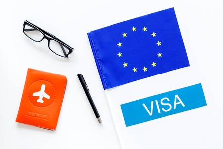 Schengen .   Europe concept. Text  near passport cover and european flag on white background top view