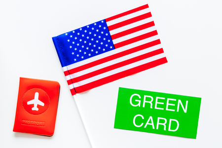 United States of America permanent resident cards. Immigration concept. Text green card near passport cover and US flag top view on white background Фото со стока