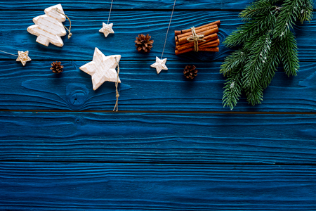 Spruce branch, cones and vintage toys in shape of spruce and stars on blue background for decoration on chrismas or new year top view copy space