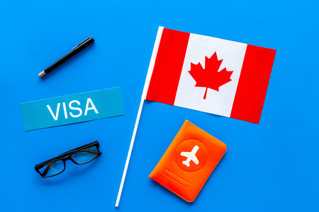 Visa to Canada concept. Text visa near passport cover and canadian flag on blue background top view 版權商用圖片