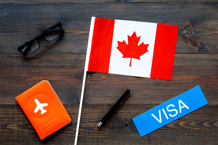 Visa to Canada concept. Text visa near passport cover and canadian flag on dark wooden background top view