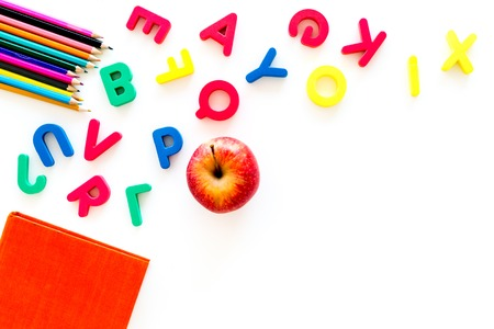 Primary school concept. Letters of english alphabet, book, apple and color pencils on white background top view copy space