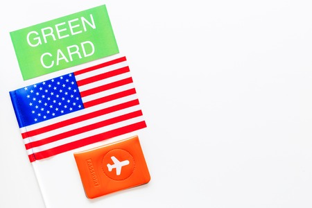 United States of America permanent resident cards. Immigration concept. Text green card near passport cover and US flag top view on white background.
