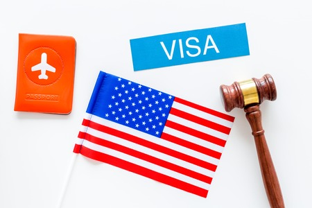 Visa to United States of America concept. Text visa near passport cover and USA flag on white background top view.