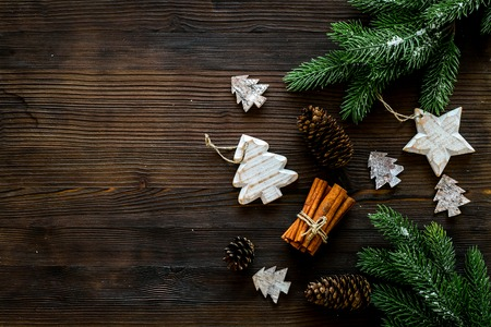 Christmas background. Spruce branch, cones and toys for decoration on dark wooden background top view copy space