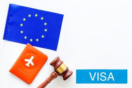 Schengen visa. Visa to Europe concept. Text visa near passport cover and european flag, judge hammer on white background top view