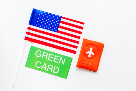 United States of America permanent resident cards. Immigration concept. Text green card near passport cover and US flag top view on white background copy space 版權商用圖片
