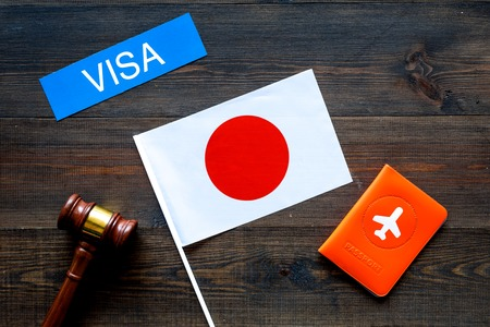 Visa to Japan concept. Text visa near passport cover and japanese flag, hammer on dark wooden background top view Фото со стока