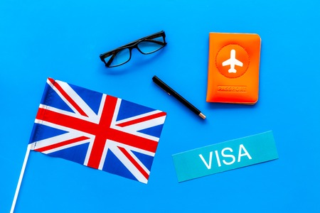 Visa to Britain concept. Text visa near passport cover and british flag on blue background top view