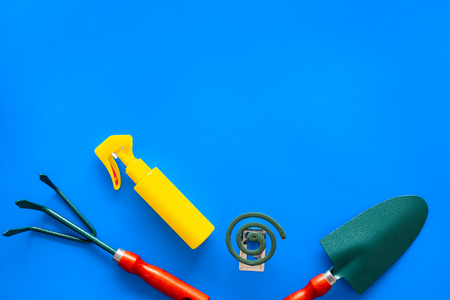Mosquito protection for garden. Mosquito coil and spray near garden tools on blue background top view. Archivio Fotografico - 108959355