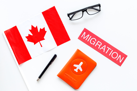Immigration to Canada concept. Text immigration near passport cover and canadianflag on white background top view.