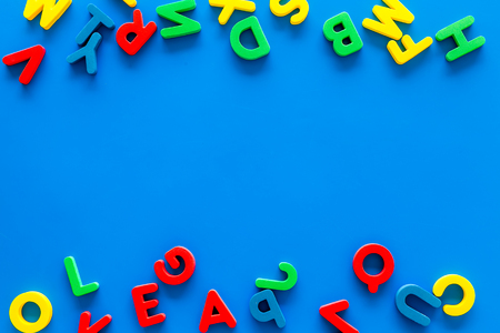 Alphabet for kids concept. English letters in disorder on blue background top view.
