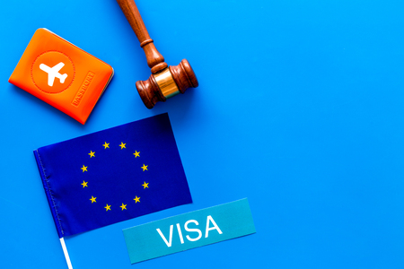 Schengen visa. Visa to Europe concept. Text visa near passport cover and european flag, judge hammer on blue background top view