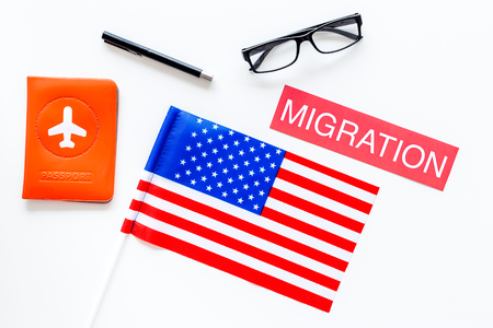 Immigration to United States of America concept. Textimmigration near passport cover and USA flag on white background top view Stock Photo