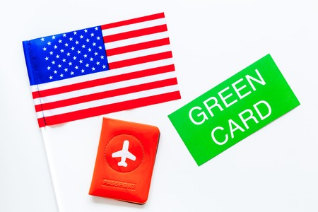 United States of America permanent resident cards. Immigration concept. Text green card near passport cover and US flag top view on white background 版權商用圖片