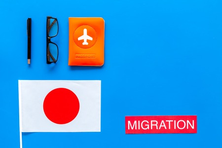 Immigration to Japan concept. Text immigration near passport cover and japanese flag on blue background top view copy space