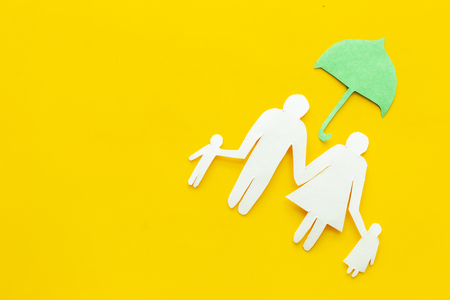 Illustration of social security concept. Financial protection. Family silhouette, cutout under umbrella on yellow background top view copy space