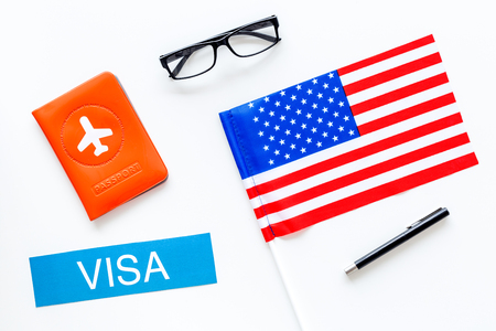 Visa to United States of America concept. Text visa near passport cover and USA flag on white background top view